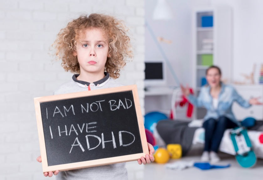Boy holding chalkboard up saying I am not bad, I just have adhd