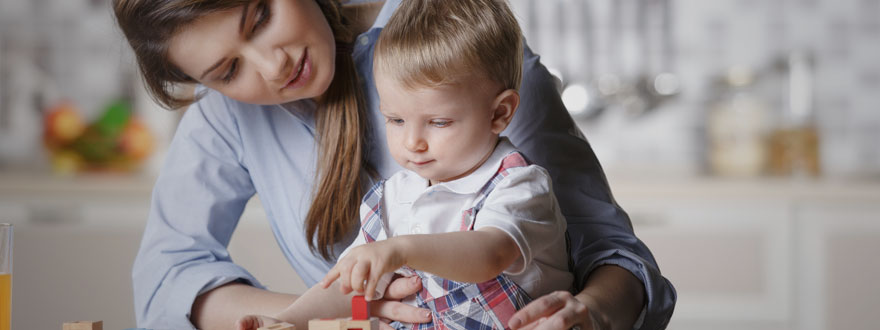 Toddler with his mother playing with blocks