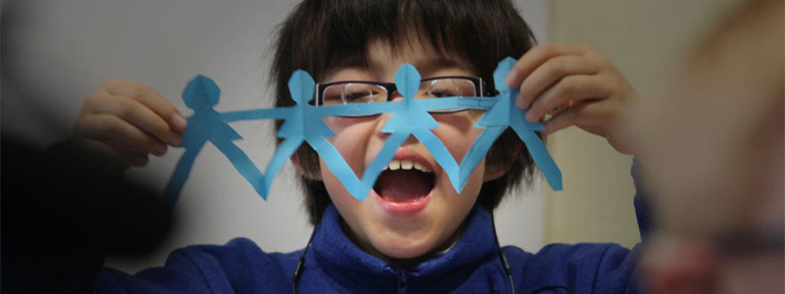 Child with glasses holding up paper men cutouts